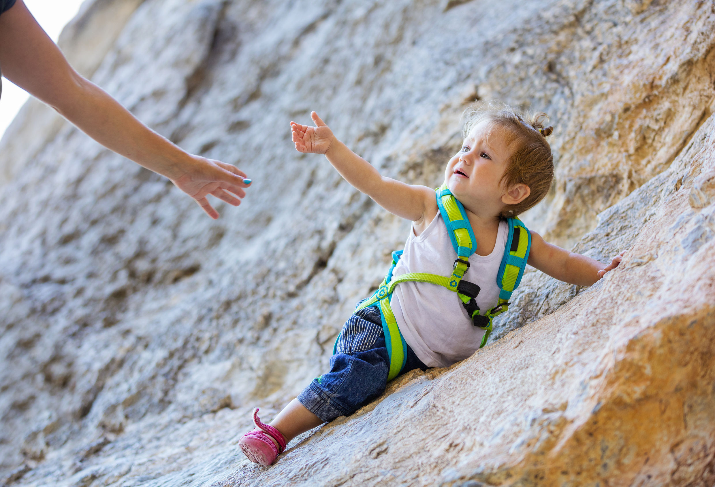 Little girl in climbing gear stretching out hand