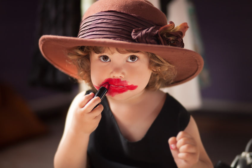 Little girl trying mom's lipstick. Growing up concept