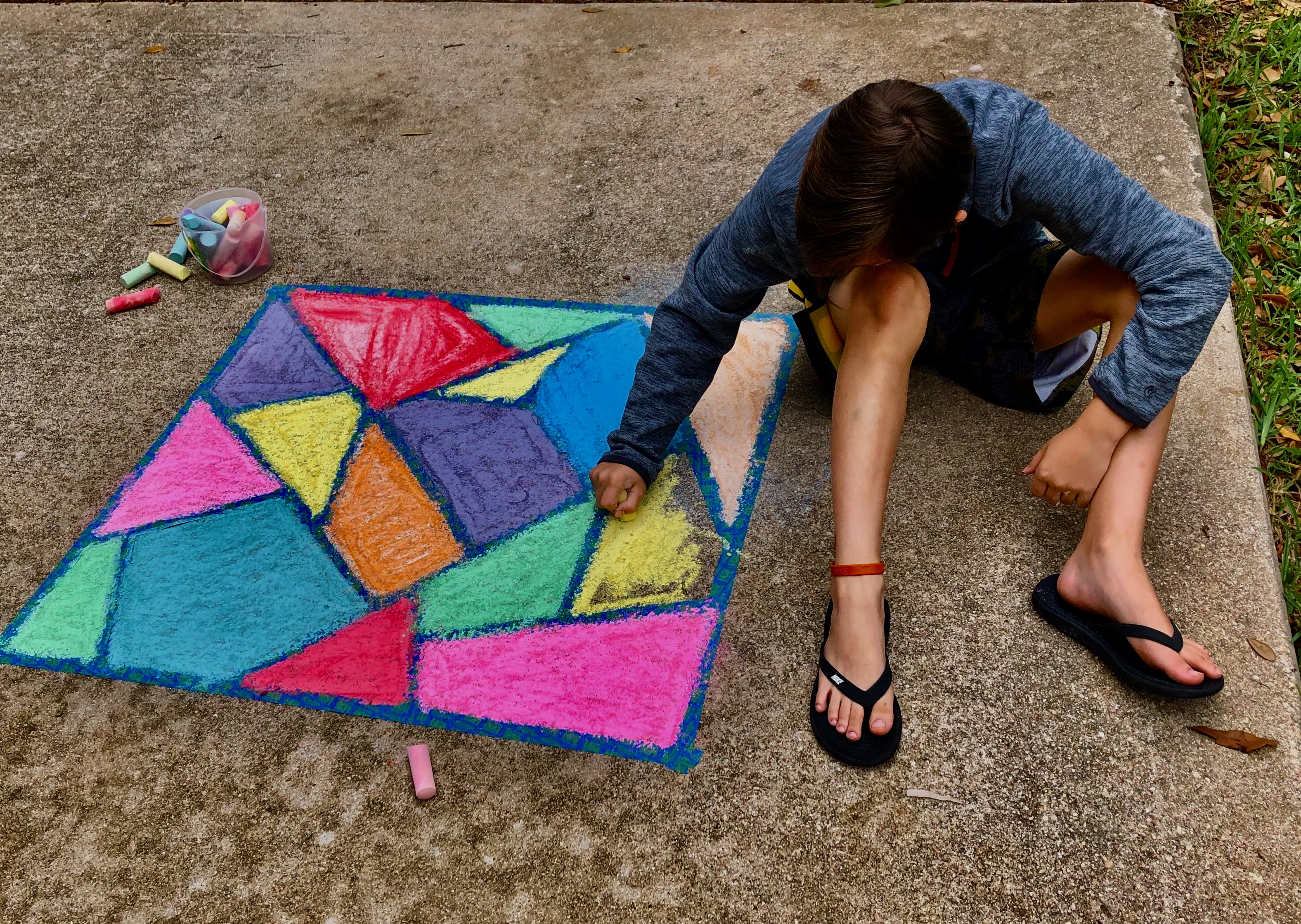kid drawing chalk art on sidewalk
